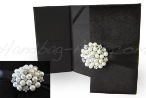 Pearl brooch embellished black velvet invitation folder